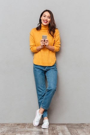Full length image of Cheerful brunette woman in sweater holding smartphone and looking at the camera over gray background 免版税图像