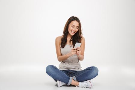 Szczęśliwa brunetka kobieta siedzi na podłodze i pisze wiadomość na smartfonie na szarym tle