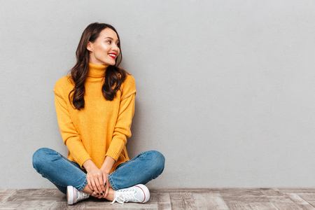 Happy brunette woman in sweater sitting on the floor and looking away over gray background