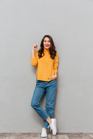 Full length image of Happy brunette woman in sweater with arms in pockets looking at the camera over gray background