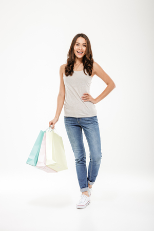 Full-length picture of glad woman holding lot of packs with purchases expressing satisfaction and happiness after shopping over white wall
