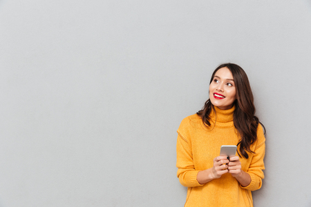 Smiling brunette woman in sweater holding smartphone and looking away over gray background 免版税图像