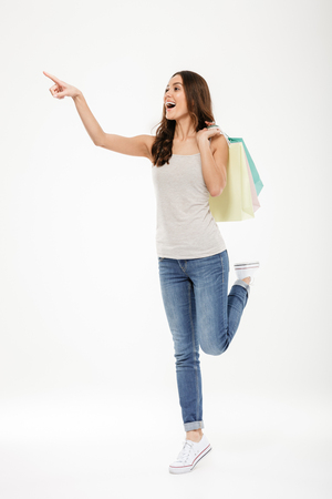 Full-length portrait of trendy woman pointing finger away and holding many shopping bags isolated over white wall