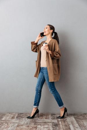 In voller Länge einer überzeugten jungen asiatischen Frau , die am Handy beim Gehen und Tasse Kaffee über grauem Hintergrund spricht