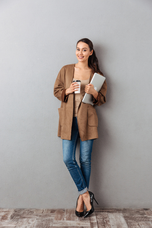 Full length portrait of a pretty young asian woman holding cup of coffee and laptop computer while standing and looking at camera over gray background