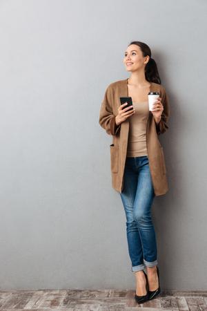 integral de una hermosa mujer joven asiática sosteniendo teléfono móvil mientras está de pie y sosteniendo la taza de café sobre fondo gris