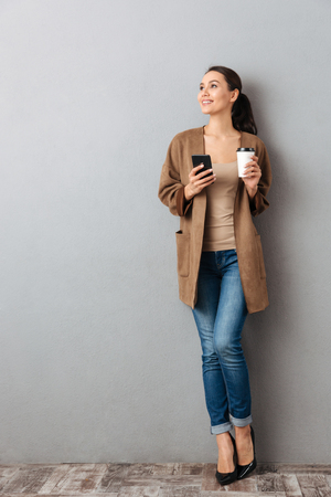 Full length of a beautiful young asian woman holding mobile phone while standing and holding cup of coffee over gray background Foto de archivo