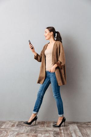 Volledige lengte van een gelukkige jonge Aziatische vrouw die mobiele telefoon met behulp van terwijl het lopen over grijze achtergrond