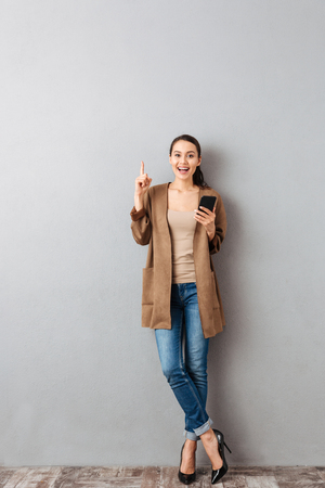 Full length of a cheerful young asian woman pointing finger up while standing and holding mobile phone over gray background Banque d'images