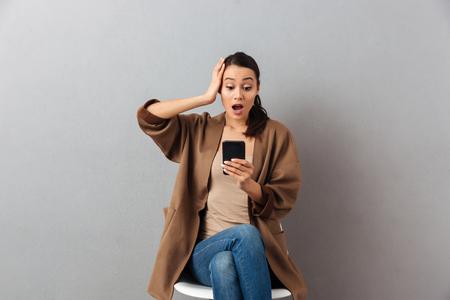 retrato de una mujer asiática pensativa que mira el teléfono móvil mientras está sentado en una silla sobre fondo gris
