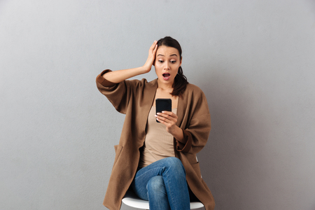 Portrait of an astonished casual asian woman looking at mobile phone while sitting on a chair over gray background