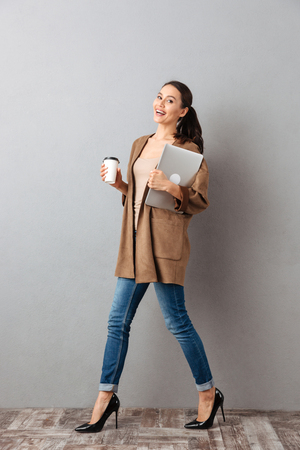 Full length portrait of a smiling young asian woman holding cup of coffee and laptop computer while walking and looking at camera over gray background