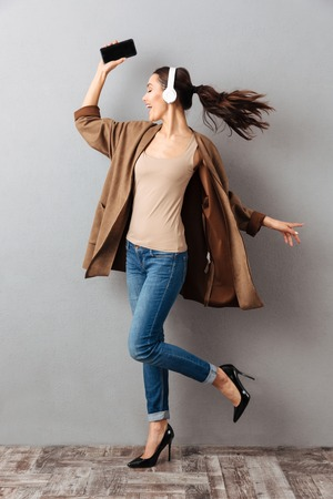 Full length portrait of a cheery young asian woman listening to music with headphones while holding mobile phone and dancing over gray background