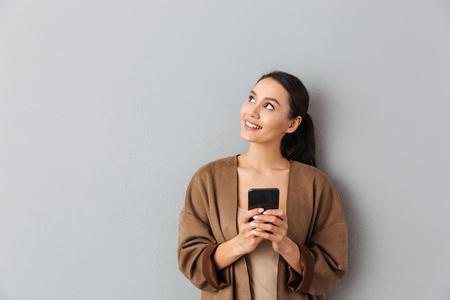 Portret szczęśliwa młoda azjatykcia kobieta trzyma telefon komórkowy stojąc i patrząc od hotelu na szarym tle