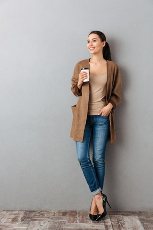 Full length of a smiling young asian woman standing and holding cup with coffee over gray background