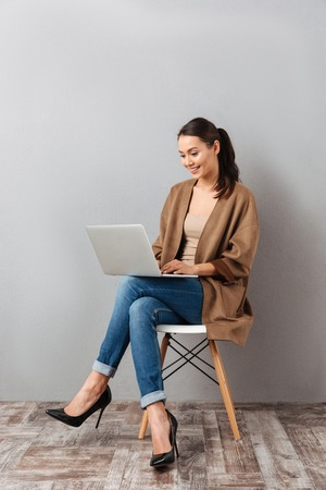 Full length portrait of a happy casual asian woman holding laptop computer while sitting on a chair over gray background