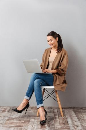 Ganzaufnahme einer glücklichen asiatischen Asiatin , die Laptop-Computer beim Sitzen auf einem Stuhl über grauem Hintergrund hält