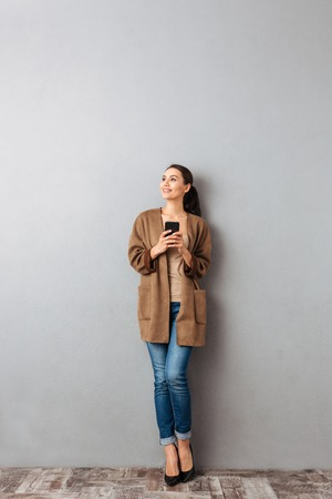 Full length of a happy young asian woman holding mobile phone while standing and looking away over gray background Stock Photo