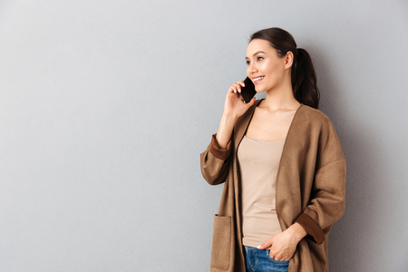 Portrait of a smiling young asian woman talking on mobile phone while standing and looking away at copy space over gray background