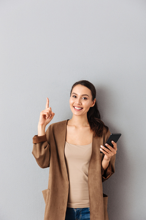 Portrait of a joyful young asian woman holding mobile phone while standing and pointing finger up at copy space over gray background