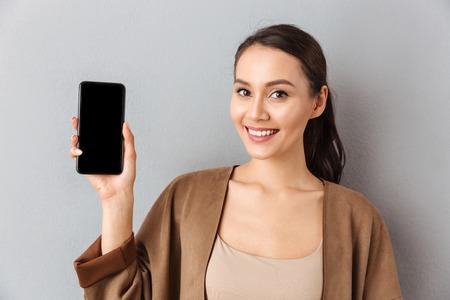 Chiuda su di giovane donna asiatica sorridente che mostra il telefono cellulare dello schermo in bianco mentre stanno e esaminando la macchina fotografica sopra fondo grigio