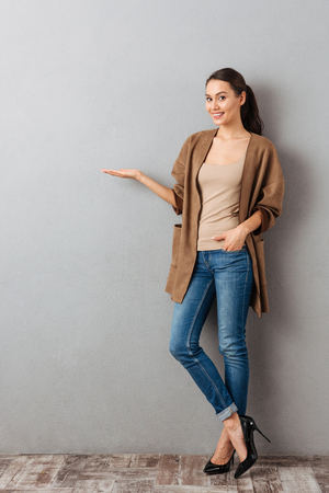 Full length of a happy young asian woman standing and presenting copy space on her palm over gray background