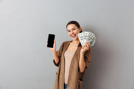 Portrait of a delighted young asian woman holding bunch of money banknotes and showing blank screen mobile phone over gray background