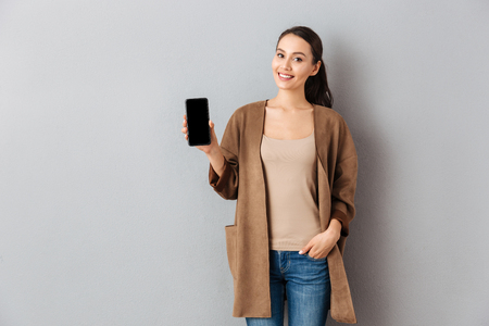 Portrait of a satisfied young asian woman showing blank screen mobile phone while standing and looking at camera over gray background