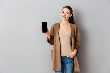 Portrait, satisfait, jeune, femme asiatique, projection, écran vide, téléphone portable, debout, regarder appareil-photo, sur, les, fond gris