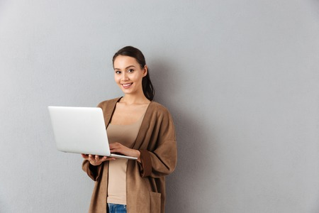 Portrait of a happy young asian woman holding laptop computer while standing and looking at camera over gray background