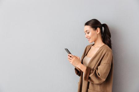 Portret atrakcyjnej młodej azjatyckiej kobiety korzystającej z telefonu komórkowego, stojąc z kopią przestrzeni na szarym tle