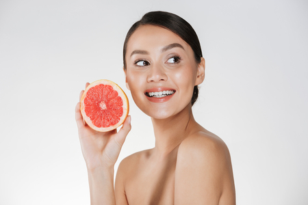 Close up image of glad woman with healthy fresh skin holding juicy grapefruit and looking aside with smile isolated over white background