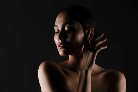 Portrait of feminine tender woman with sensual look posing at camera looking aside in low lights isolated over black background Stock fotó