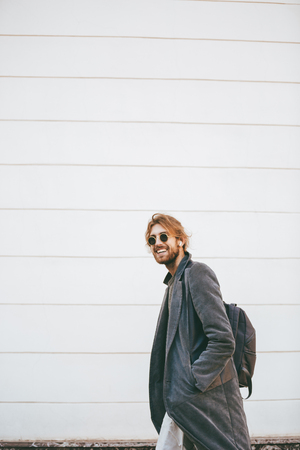 Portrait of a smiling bearded man wearing sunglasses and coat walking on a city street and looking away