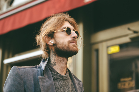 Portrait of a stylish bearded man in earphones wearing sunglasses and coat walking on a city street outdoors