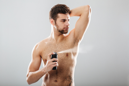 Portrait of handsome shirtless guy spraying perfume over his muscular body, isolated over gray background