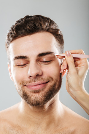 Portrait of relaxed man with closed eyes smiling while female hand plucking his eyebrows with tweezers, isolated over gray background