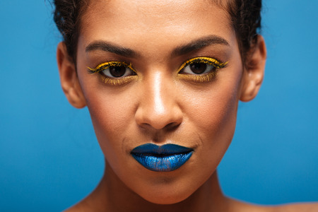 Closeup stylish photo of gorgeous mixed-race woman with colorful cosmetics on face looking on camera isolated over blue background