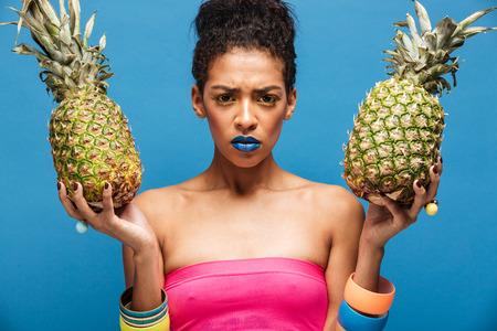 Portrait of serious mulatto woman with stylish appearance frowning face being upset while holding two ripe pineapples in both hands isolated over blue wall