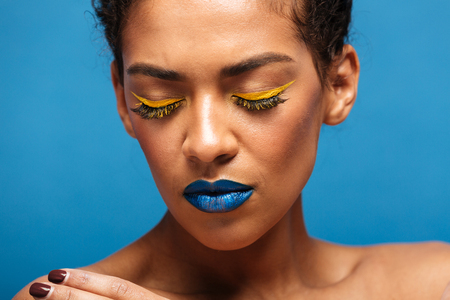 Closeup stylish photo of relaxed mixed-race woman with colorful cosmetics on face posing on camera with closed eyes isolated over blue background Banco de Imagens