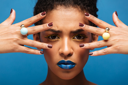 Stylish concentrated afro woman with colorful makeup demonstrating rings on her fingers keeping hands at face isolated over blue wall