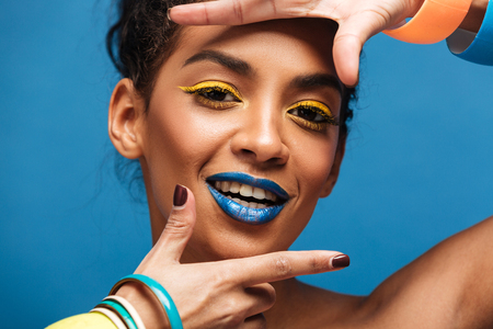 Horizontal photo of stylish mulatto woman with colorful makeup and curly hair in bun gesturing on camera with smile isolated over blue wall Stock Photo
