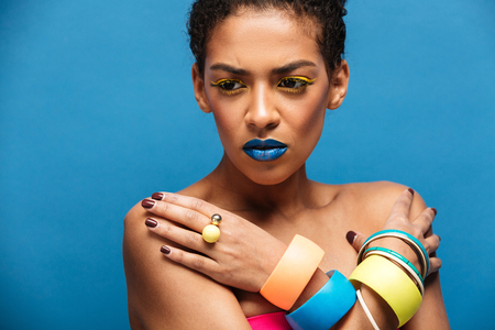 Colorful photo of tense or disappointed mixed-race woman with trendy makeup and accessories posing with crossed hands on chest over blue wall