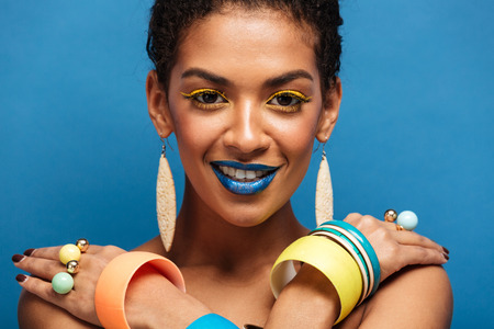 Closeup photo of sensual naked mulatto woman with fashion makeup and accessories posing on camera with crossed hands on shoulders over blue