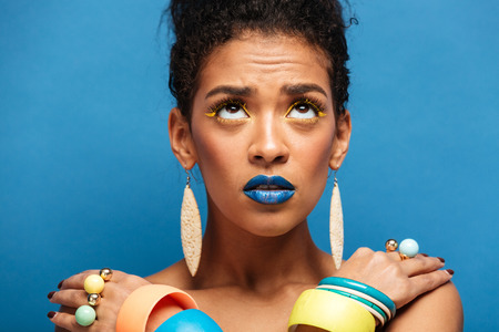 Colorful photo of thrilled mixed-race woman with trendy makeup and accessories looking upward with crossed hands on shoulders over blue wall Stock Photo
