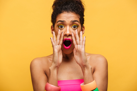 Bright image of excited stylish african american woman emotionally shouting or calling on camera putting hands at mouth isolated over yellow wall