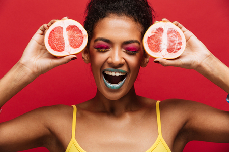 Food fashion photo of delighted afro american woman having fun holding two halves of fresh ripe grapefruit at face isolated over red wall