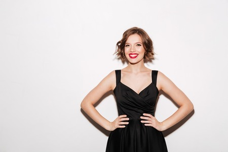 Portrait of a happy girl dressed in black dress standing with arms on hips isolated over white background