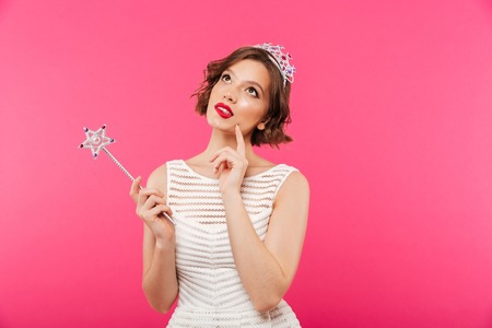 Portrait of a pensive girl wearing crown and holding magic wand while looking up isolated over pink background