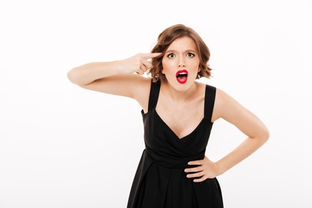 Portrait of an angry girl dressed in black dress showing finger at her head gesture isolated over white background
